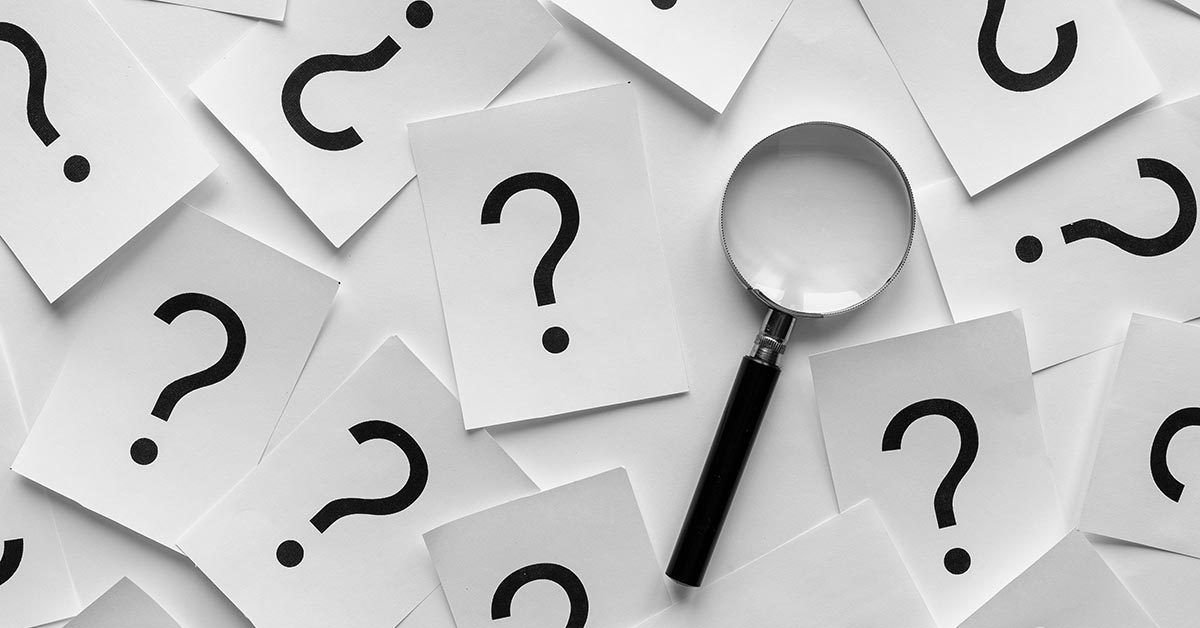 Background pattern of random question marks printed on white cards with a magnifying glass overlying them