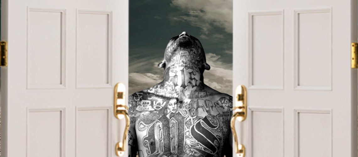 ms 13 gang member standing at open door to border between mexico and us
